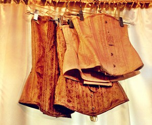 vintage corsets hanging on hangers