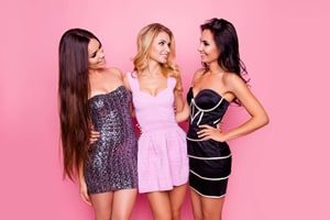 Three girls looking at each other infront of pink background