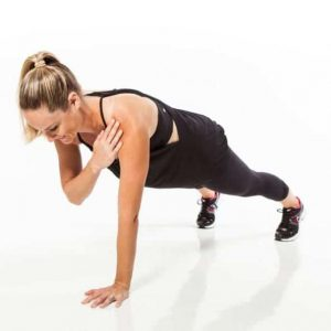 Woman is doing one arm tick tock plank exercise.
