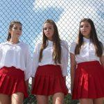 three teenage girls standing outside