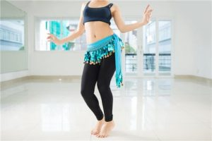 Belly dancer in legging and hip scarf dancing in the class.