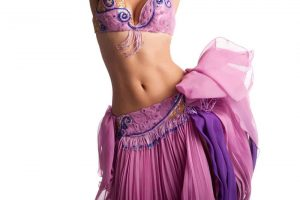 Torso of a female belly dancer wearing a pink costume and shaking her hips. Isolated on white.