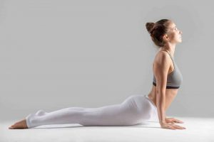 Young attractive woman practicing yoga, stretching in Cobra exercise, Bhujangasana pose, working out wearing sportswear, indoor full length, isolated against grey studio background.