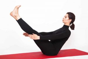 Beautiful athletic girl in black suit doing yoga. naukasana asana - boat pose. Isolated on white background.