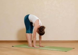 Caucasian woman is practicing yoga at studio (padahastasana).