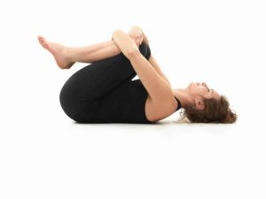 Caucasian woman on the floor, in relaxed yoga pose, side view, dressed in black on white background.