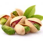 Pistachios with leaves on white background.