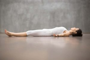 Side view portrait of beautiful young woman working out against grey wall, resting after doing yoga exercises, lying in Savasana (Corpse or Dead Body Posture), relaxing. Full length.