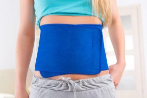 Woman wearing neoprene slimming belt at home.