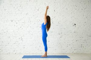 Young attractive woman practicing yoga, standing in mountain exercise, Tadasana pose, working out, wearing sportswear, blue jumpsuit, indoor full length, white loft studio background. Side view.
