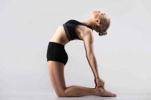 Sporty beautiful young woman practicing yoga, doing Ushtrasana, Camel Pose, working out wearing black sportswear, studio, full length.