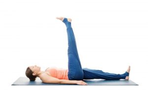 Woman doing yoga asana Uttanpadasana - lying down straight leg raise pose posture isolated on white background.