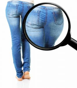 Thin woman in blue jeans isolated on white background with fat body in magnifier.