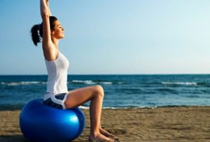 Woman doing yoga on exercise ball by beach