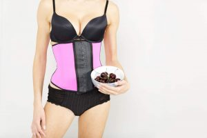 Young woman wearing a waist training corset in black underwear which is the new craze for looking slim.