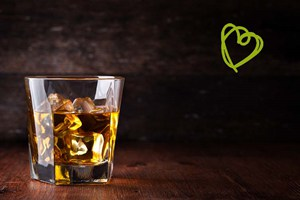 A glass of whiskey with a green drawing heartshape