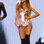 Ariana Grande wearing a golden stage corset dress