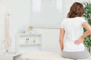 Woman sitting on a table while touching her back