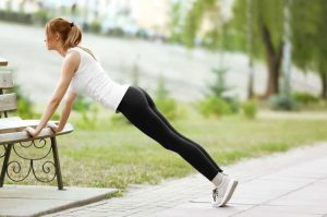 Young woman performing push-ups from a bench in a park.