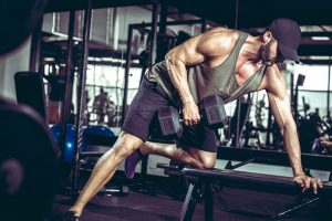 Young man doing one-arm dumbbell rows