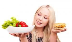 Thoughtful young woman holding a hamburger with chicken and plate with vegetables, isolated against white background.