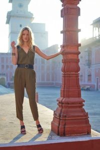 Corset belt over an olive jumpsuit