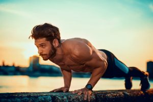Young man doing push ups outdoors