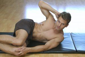 Man doing side crunch on floor