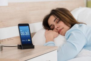 Young woman sleeping on bed with alarm on mobile phone