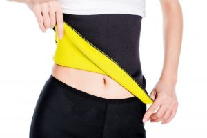 Woman wearing a slimming belt on white background