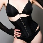 Sexy woman wearing a black waist trainer