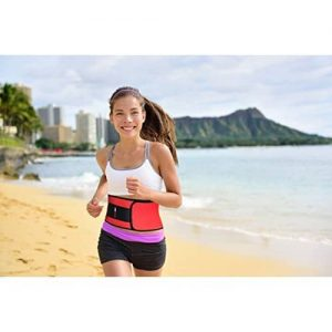 Woman running with waist trimmer belt on by the beach