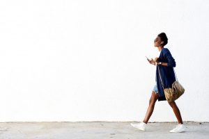 Full length side view portrait of trendy young black woman walking outdoors and listening to music on her mobile phone.