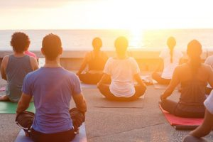 Group of people doing yoga under sunset